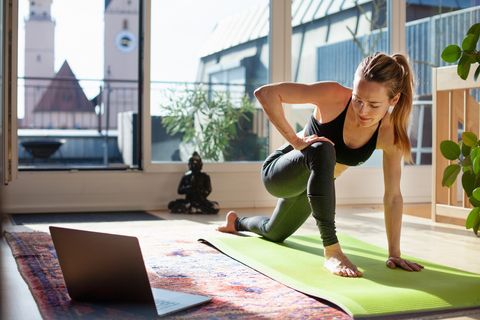 woman-exercising-at-home-in-front-of-her-laptop-royalty-free-image-1586364340.jpg